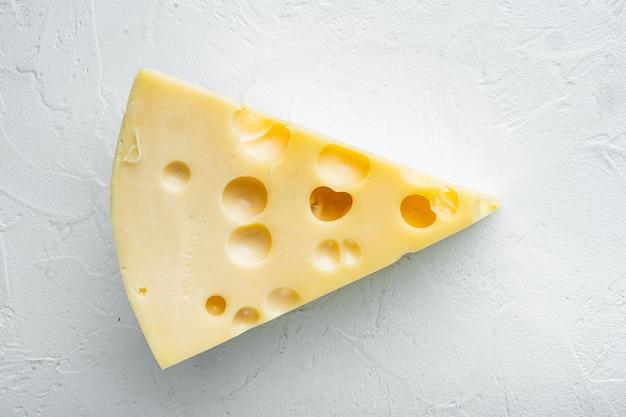 Zestaw serów maasdam, na białej kamiennej powierzchni, widok z góry na płasko