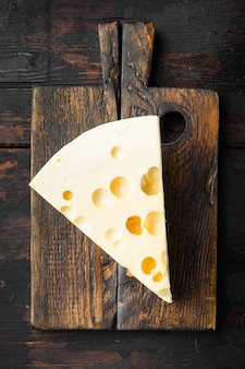 Zestaw serów maasdam, na starym ciemnym drewnianym stole, widok z góry na płasko