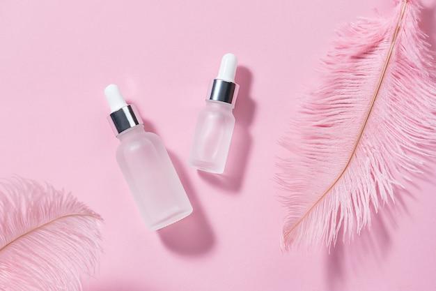 Zestaw serum do pielęgnacji skóry na różowym pastelowym tle ze strusimi piórami koncepcja pielęgnacji skóry