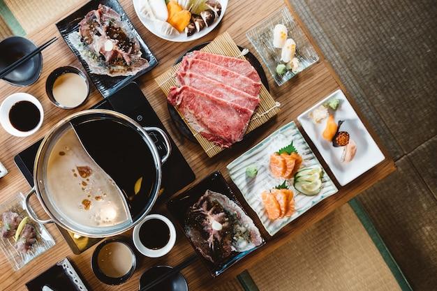 Zestaw shabu w tym rzadkie plasterki wołowiny wagyu a5, shabu shoyu i klarownej bazy, łososia, sushi.