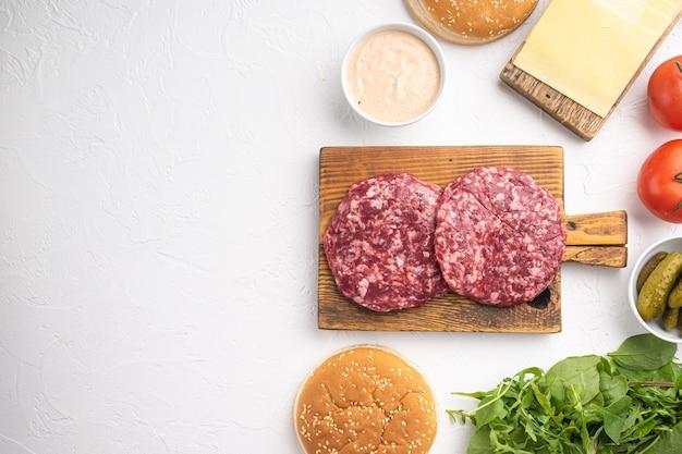Zestaw składników do burgera wołowego, na białym kamieniu