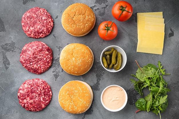 Zestaw składników do burgera wołowego, na szarym kamieniu