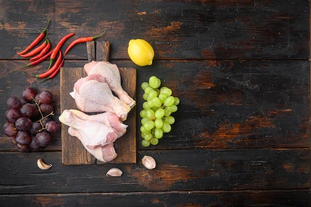 Zestaw składników niespodzianki słodkiego kurczaka, z winogronami i pietruszką, na drewnianej desce do krojenia, na starym ciemnym drewnianym stole, widok z góry na płasko