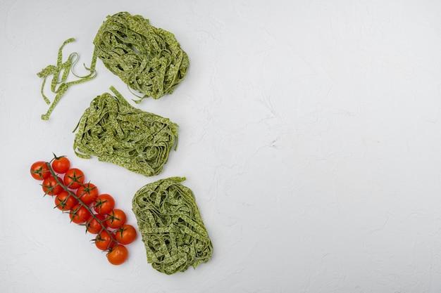 Zestaw składników zielonego makaronu, na białym tle kamiennego stołu, płaski widok z góry, z miejscem na kopię tekstu