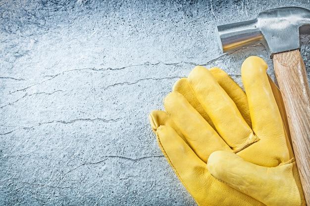 Zestaw skórzanych rękawic ochronnych młotek na metalicznym tle