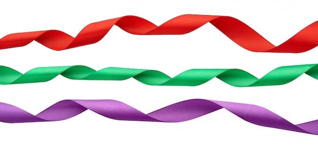 Zestaw skręconych jedwabnych wstążek czerwony, zielony, fioletowy na białym tle
