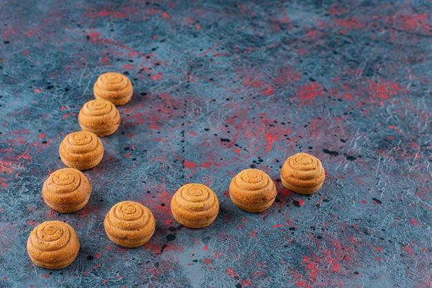 Zestaw słodkich, pysznych, świeżych okrągłych ciasteczek na ciemnej powierzchni