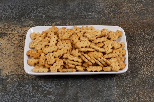 Zestaw słone krakersy na białym kwadratowym talerzu.