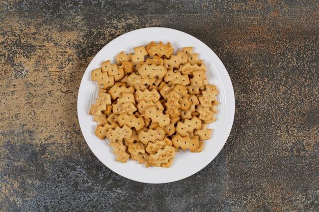 Zestaw słone krakersy na białym talerzu.