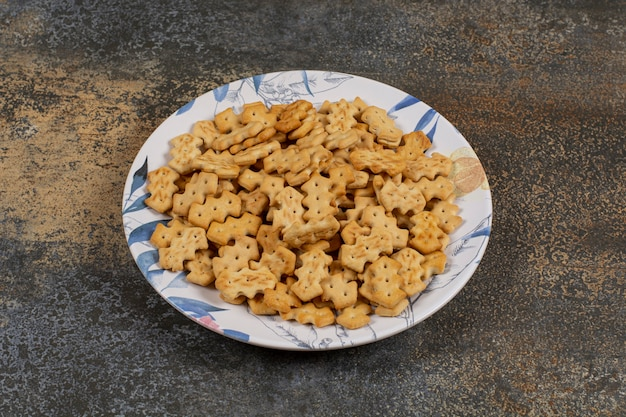 Zestaw słonych krakersów na kolorowym talerzu.