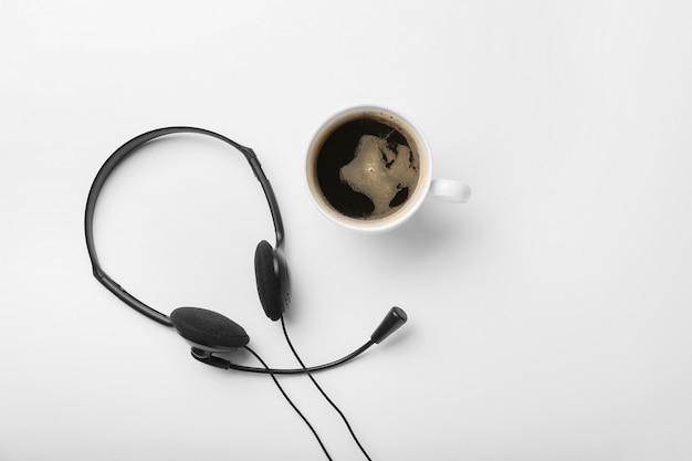 Zestaw słuchawkowy i filiżankę kawy na białym tle