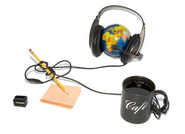 Zestaw słuchawkowy na świecie z kawą i ołówkiem na białym tle