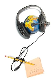 Zestaw słuchawkowy na świecie z ołówkiem i notatką na białym tle