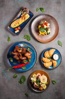 Zestaw smacznych gorących przystawek: skrzydełka z kurczaka, krewetki, nadziewana cukinia. widok z góry