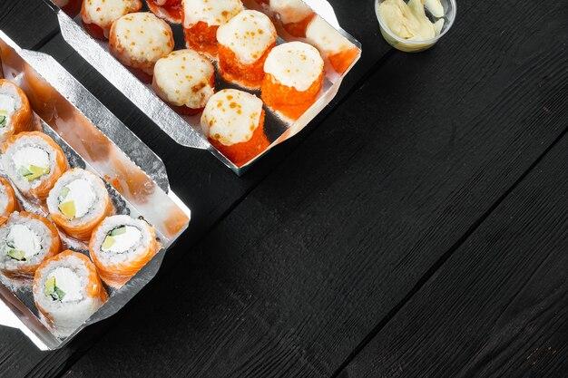 Zestaw smacznych sushi w jednorazowych pudełeczkach na czarnym drewnianym stole