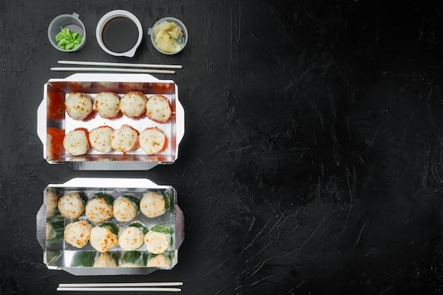 Zestaw smacznych sushi w jednorazowych pudełeczkach na czarnym kamieniu