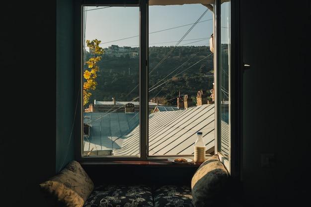 Zestaw śniadaniowy butelki mleka i ciasteczek przy oknie w ciepłym porannym świetle słonecznym.