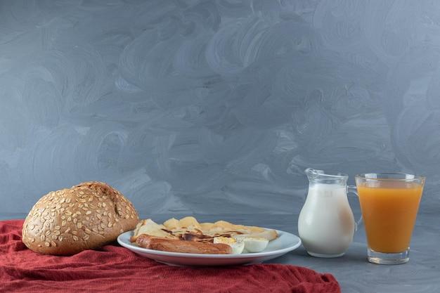 Zestaw śniadaniowy na czerwonym obrusie na marmurowym stole.