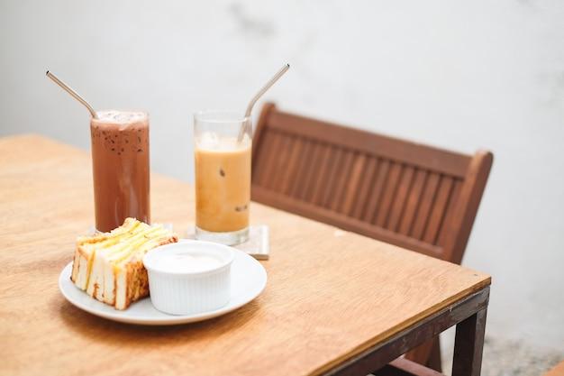 Zestaw śniadaniowy składa się z jajecznego chleba (kanapki) z sosem jajecznym, lodowym kakao i kawy (latte) na stole - domowe jedzenie.