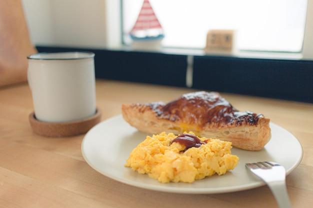 Zestaw śniadaniowy składający się z domowego ciasta kanapkowego z jajecznicą i czarną kawą.