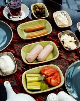 Zestaw śniadaniowy z kiełbasami, pomidorem i serem ogórkowym, czarną herbatą oliwkową