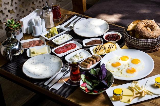 Zestaw śniadaniowy z kiełbasami z jajek, serem maślanym, miodem i zieloną sałatą