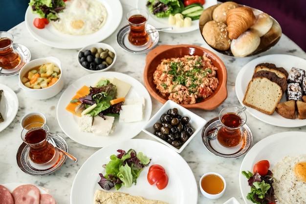 Zestaw śniadaniowy z widokiem z góry jajecznica z pomidorami różne sery warzywa oliwki miód z herbatą i chlebem na stole