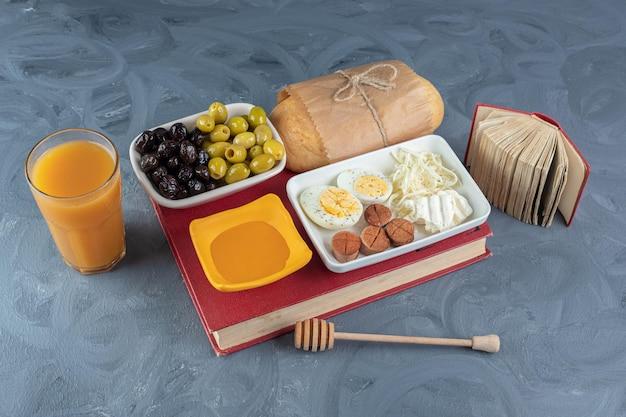Zestaw śniadaniowy zawinięty na książce, obok mały zeszyt, łyżka do miodu i szklanka soku na marmurowej powierzchni.