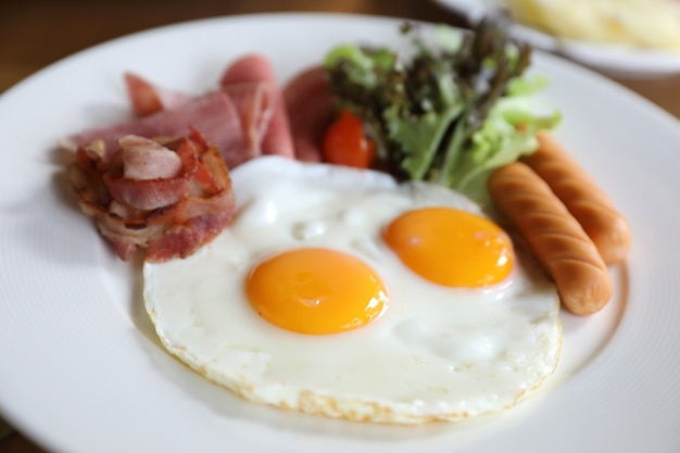 Zestaw śniadaniowy ze smażonymi jajkami, bekonem, kiełbasami, fasolą, tostami, świeżą sałatką i owocami na drewnianym stole