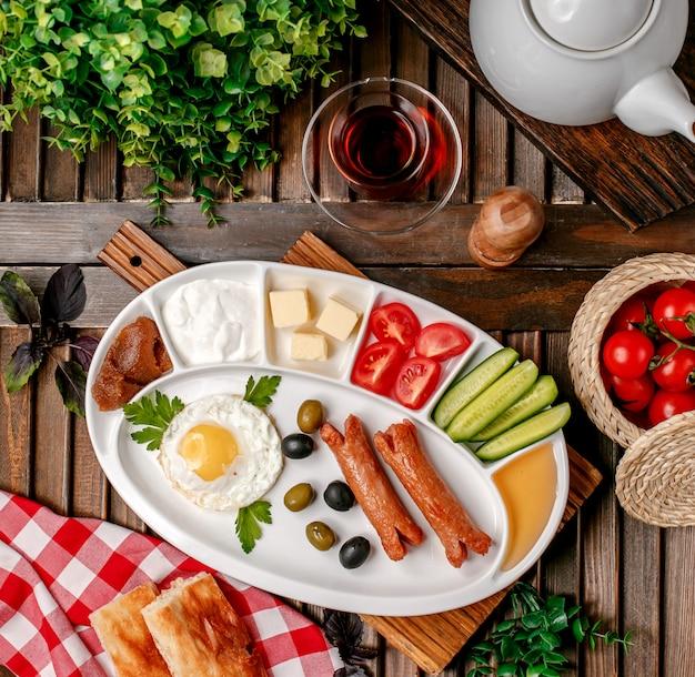 Zestaw śniadaniowy ze smażonymi kiełbaskami jajek i warzyw