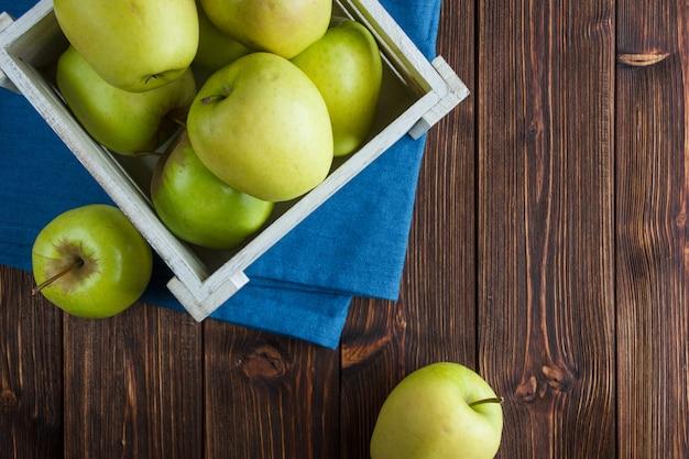 Zestaw sok jabłkowy i zielone jabłka w drewnianym pudełku na tle tkaniny i tkaniny. leżał płasko. miejsce na tekst