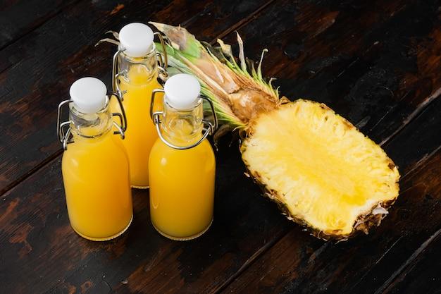 Zestaw soku ananasowego, na starym ciemnym tle drewnianego stołu
