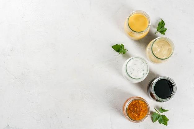 Zestaw sosów do sałatek: sos winegret, musztarda, majonez lub ranczo, balsamiczny lub sojowy, bazylia z jogurtem. ciemnobiały betonowy stół. skopiuj widok z góry