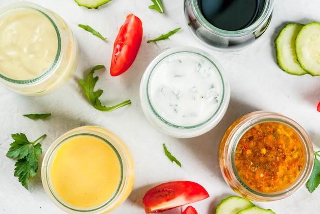 Zestaw sosów do sałatek: sos winegret, musztarda, majonez lub ranczo, balsamiczny lub sojowy, bazylia z jogurtem. ciemnobiały betonowy stół, z zielenią, warzywami na sałatkę. skopiuj widok z góry