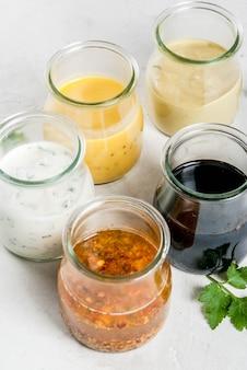 Zestaw sosów do sałatek: sos winegret, musztarda, majonez lub ranczo, balsamiczny lub sojowy, bazylia z jogurtem. ciemnobiały betonowy stół.
