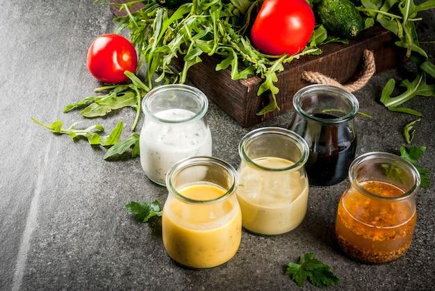 Zestaw sosów do sałatek: sos winegret, musztarda, majonez lub ranczo, balsamiczny lub sojowy, bazylia z jogurtem. stół z ciemnego kamienia. z zieleni, warzyw na sałatkę.