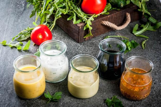 Zestaw sosów do sałatek: sos winegret, musztarda, majonez lub ranczo, balsamiczny lub sojowy, bazylia z jogurtem. stół z ciemnego kamienia.