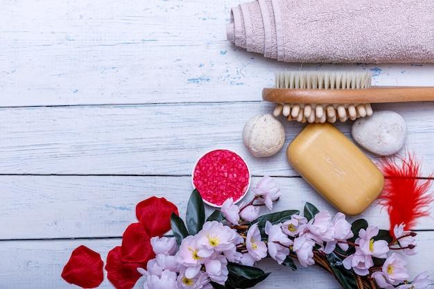Zestaw spa lub koncepcja z naturalnych produktów ekologicznych na białym drewnianym stole. batonik mydlany i płyn. różowa sól do aromaterapii. widok z góry z miejsca kopiowania.