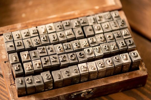 Zestaw specjalnych sztabek z łacińskimi literami i cyframi arabskimi w otwartym drewnianym pudełku, które służą do wykonywania nadruków na miękkiej powierzchni