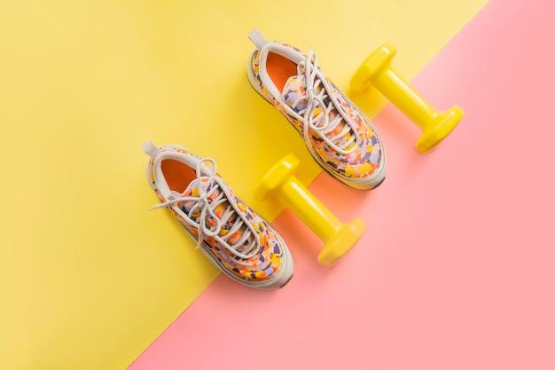 Zestaw sportowca z kobiecymi trampkami do biegania i hantlami żółto-różowym tle.