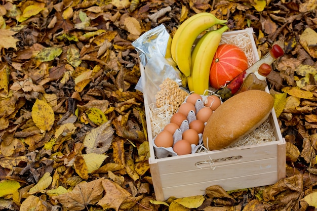 Zestaw spożywczy: banan, jajka, orzechy, dynia, kawa, pieczywo, oleje w drewnianym pudełku na tle jesiennych żółtych liści.