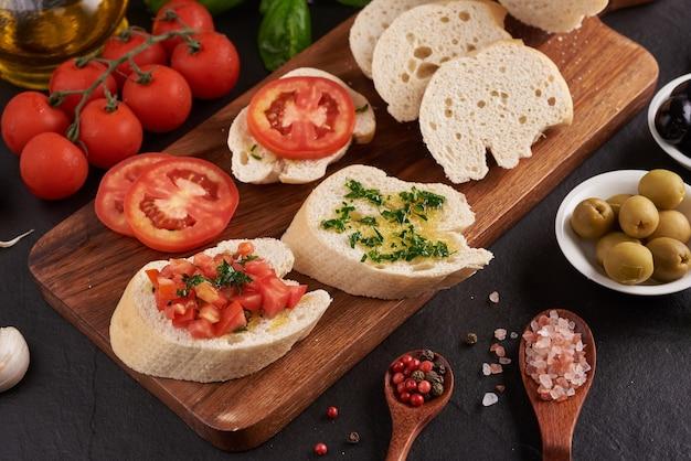 Zestaw śródziemnomorskich przekąsek. oliwki, oliwa, zioła i ciabatta w plasterkach na drewnianej desce na czarnej desce łupkowej na ciemnej powierzchni, soczyste pomidory na świeżym pieczywie, pesto jako polewa. widok z góry. leżał na płasko