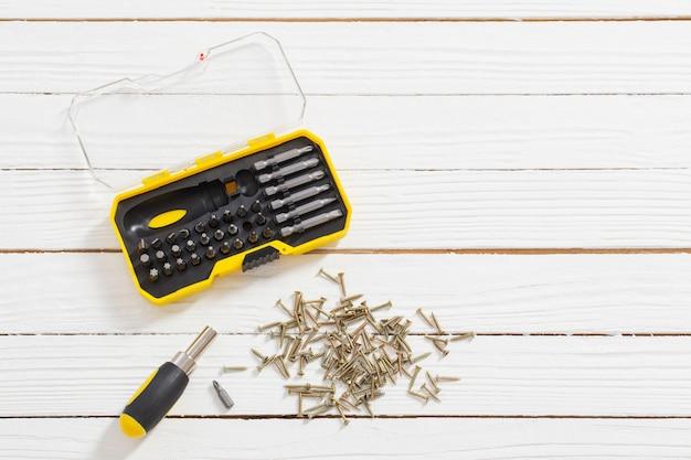 Zestaw śrubokrętów i śrub metalowych na białym tle drewnianych