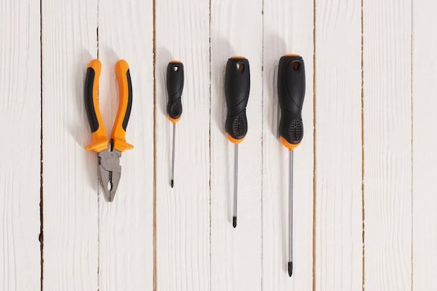 Zestaw śrubokrętów i szczypiec na białej powierzchni drewnianej