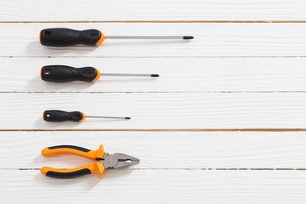 Zestaw śrubokrętów i szczypiec na białym drewnianym stole