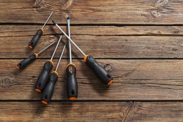 Zestaw śrubokrętów na ciemnym starym drewnianym stole
