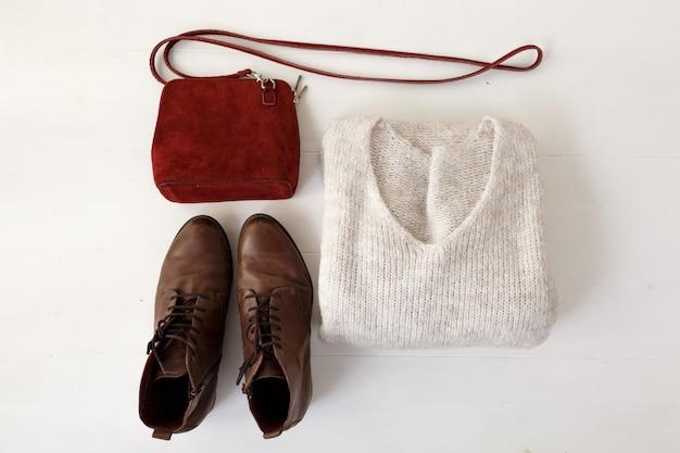 Zestaw starannie rozplanowanej stylowej odzieży damskiej i butów na białym tle widok z góry