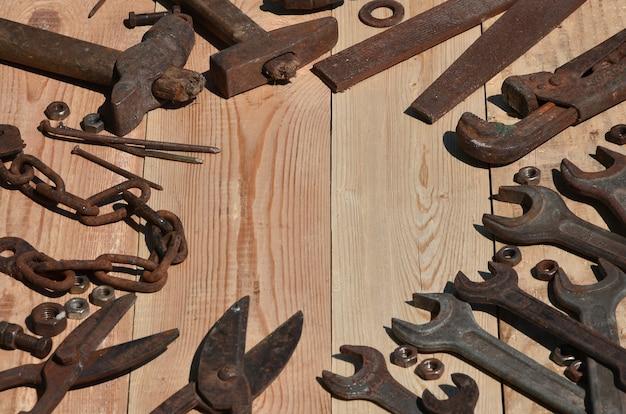 Zestaw starych i zardzewiałych narzędzi leży na drewnianym stole w warsztacie