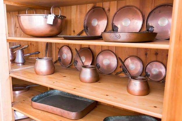 Zestaw starych ibrików i patelni na drewnianej półce