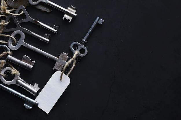 Zestaw starych kluczy do zamka. retro klucze na ciemnym tle kamienia. koncepcja wyboru drogi do osiągnięcia celu.